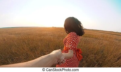 follow me. pretty portrait brunette girl goes with a man by the hand on nature field romance love. slow motion video lifestyle. girl and man walking call beckoning finger. follow me concept