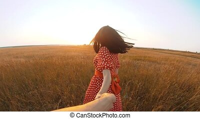 follow me. pretty portrait brunette girl goes with a man by the hand on nature field romance love. slow motion video. girl and man walking call beckoning finger. follow me follow me lifestyle