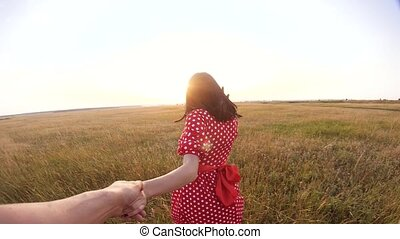 follow me. pretty portrait brunette girl goes with a man by the hand on nature field romance love. slow motion video. lifestyle girl and man walking call beckoning finger. follow me concept