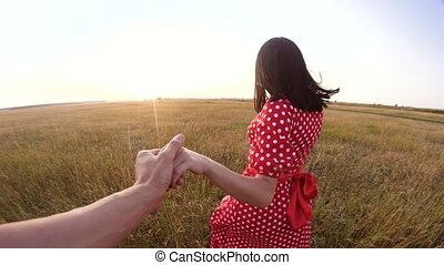 follow me. pretty portrait brunette girl goes with a man by the hand on nature field romance love. slow motion video. girl and man walking call lifestyle beckoning finger. follow me concept