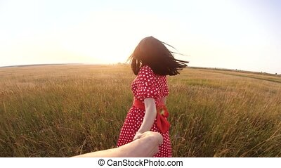 follow me. pretty portrait brunette girl goes with a man by the hand on nature field romance love. slow motion video. girl and man walking call beckoning finger. follow me lifestyle concept