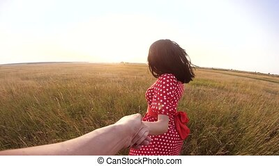 follow me. pretty portrait brunette girl goes with a man by the hand on nature field romance love. slow motion lifestyle video. girl and man walking call beckoning finger. follow me concept