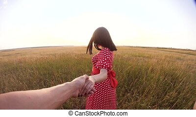 follow me. pretty portrait brunette girl goes with a man by the hand on nature field romance lifestyle love. slow motion video. girl and man walking call beckoning finger. follow me concept