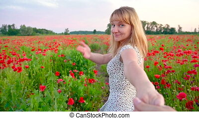 Follow me to concept. Woman holding hand of boyfriend leading through field of red poppy. Happy couple walk in meadow of flowers at sunset. POV view. Leisure in nature.