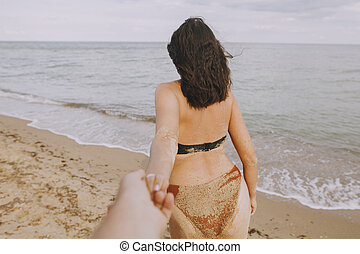 Follow me. Woman leading her man, holding hands on beach. Couple in love on summer vacation or honeymoon. Young woman with sandy tanned body holding man hand
