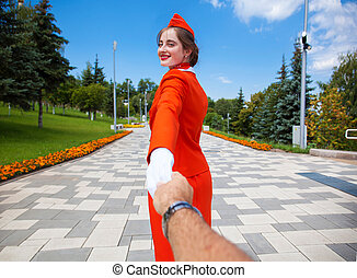 Follow Me, Young stewardess dressed in official red uniform of Airlines, Summer park outdoors