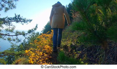 Follow shot of girl walking along the steep high shore in sunny day. Back view