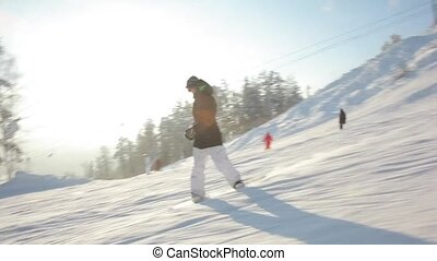 Follow Shot: Snowboarder - Snowboarder riding down the hill,...
