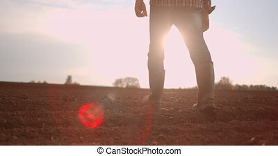 Follow to male farmers feet in boots walking through the small green sprouts of sunflower on the field. Legs of young man stepping on the dry soil at the meadow. Low angle view Close up Slow motion