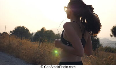Follow to sporty girl jogging in country road. Young woman in sunglasses running outdoors and listening music from smartphone. Healthy active lifestyle. Slow motion Rear back view