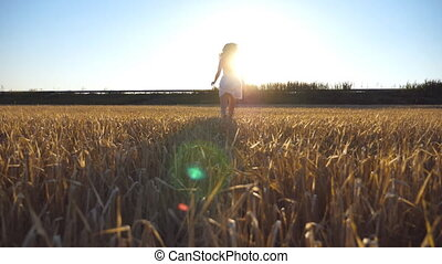Follow to young girl running along the field with sun flare at background. Woman in dress jogging at the meadow and enjoying freedom. Rear back view Slow motion