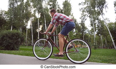 Follow to young handsome man riding a vintage bicycle...