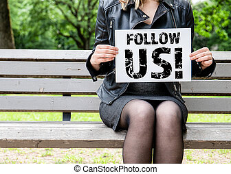 Follow us. Woman sitting on a bench