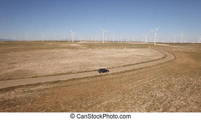 Following a black car in windmill farm, curved road - Aerial...