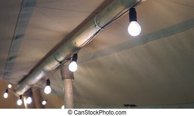 following a row of light bulbs in a tent