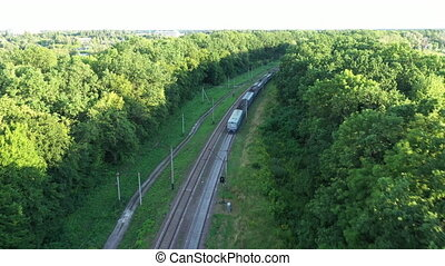 Following a train, tracking on a carriage - a train with carriages travels on railroad tracks among the green trees on a long turn.