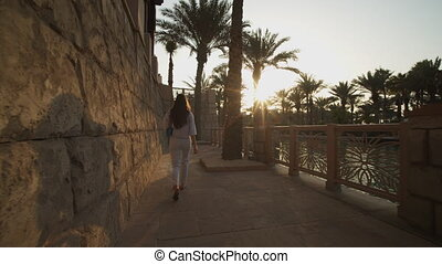 Following a woman on riverfront in luxury neighborhood in Dubai. Luxury lifestyle in residential neighborhood in United Arab Emirates 4K