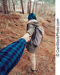 Following love - Hiker young woman with backpack holding man...