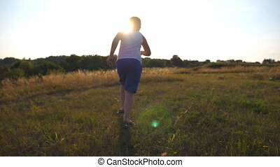 Following to young boy running on green grass at the field on sunny day. Child jogging at the lawn outdoor with sun flare. Male kid going in nature on a summer meadow. Slow motion Rear back view