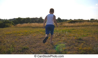 Following to young boy running on green grass at the field on sunny day. Happy smiling male kid having fun in nature on a summer meadow. Child jogging at the lawn outdoor. Slow motion Rear back view