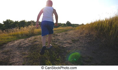 Following to young boy running on rural trail near field on...