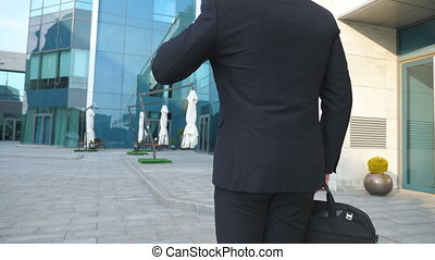 Following to young businessman with a briefcase walking near modern office building. Business man in sunglass commuting to work. Confident guy in suit going in the city. Slow motion Rear back view