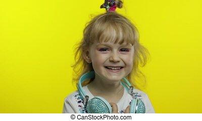 fond, appareil-photo., cou, poser, sourire, girl, écouteurs, enfant, jaune, regarder
