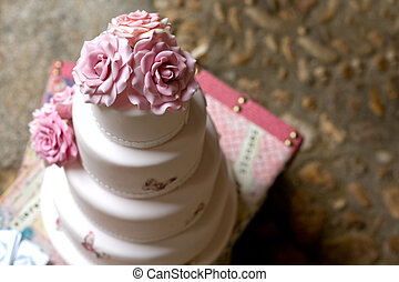 Fondant wedding cake with pink roses over vintage suitcase