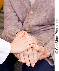 Fondness - Young doctor holds old man's hand