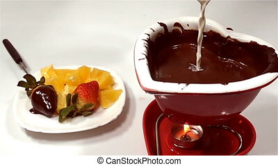 Fondue with chocolate and fruits, cream is poured into...