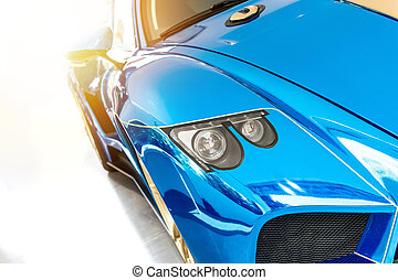 Font of a blue sport luxury car in sunset light