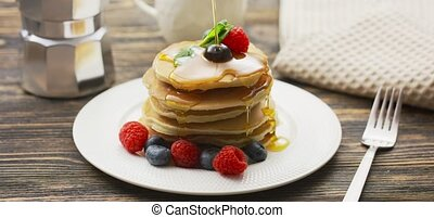 Stack of pancakes with butter and warm maple syrup