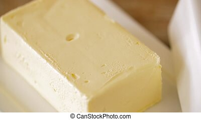 close up of butter on wooden table - food and dairy products...