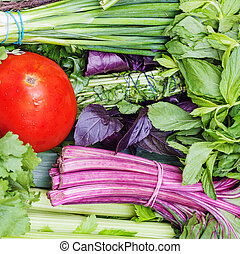 bunches of fresh cut green stuff and red tomato