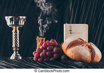 food, bible, chalice and christian cross on dark table for Holy Communion