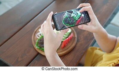 Food blogger hands using smartphone taking photo of...