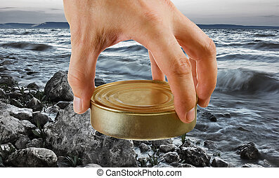 Food can in hand on a background of the sea