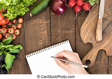 Food composition of raw vegetables, chopping board and human hand able to write something in notepad on wooden background
