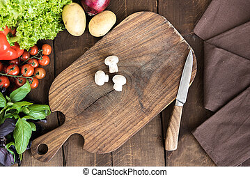 Food composition with variety of raw vegetables and mushrooms on cutting board. Organic food background