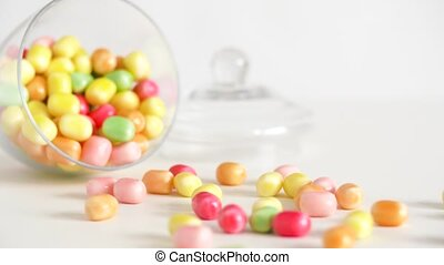 close up of scattered candy drops and jar on table - food,...