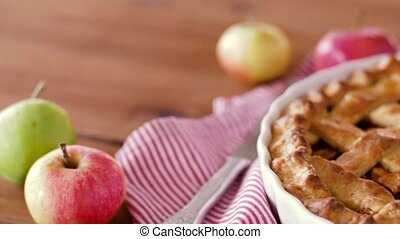 close up of apple pie and knife on wooden table - food,...