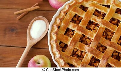 close up of apple pie on wooden table - food, culinary and...