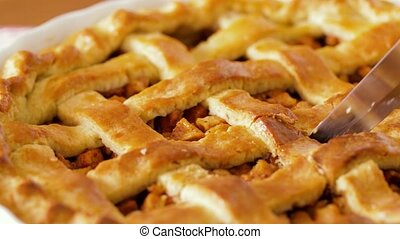 close up of apple pie slicing by knife - food, culinary and...