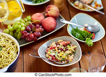 salad, fruits and pasta on wooden table