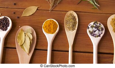 spoons with different spices on wooden table - food,...
