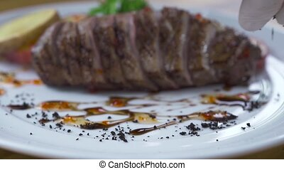 Food design concept. Chef cook decorating meat steak with sauce in dishes. Styling food in luxury restaurant. High cuisine concept.