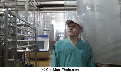 Food factory worker walks between equipment and monitors...