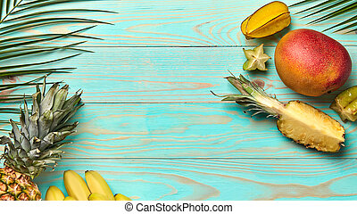 Food frame from different tropical fruits and palm branches on blue wooden background with copy space. Summer layout. Flat lay