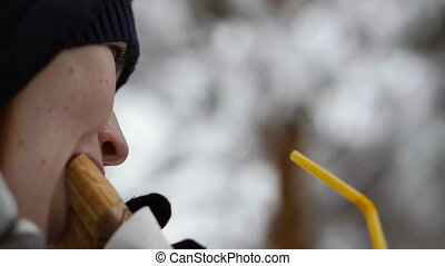 Food. Girl eating a sausage roll in a winter park