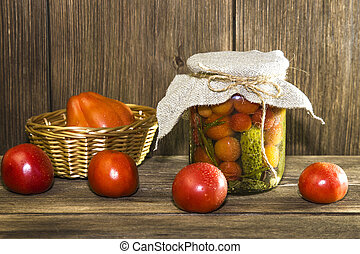 Food. Homemade canned vegetables in jars. Marinated tomatoes and cucumbers on the background of a wooden table in a rural style